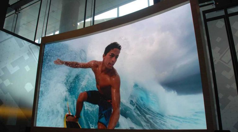 LED video walls displaying surfer riding a big wave